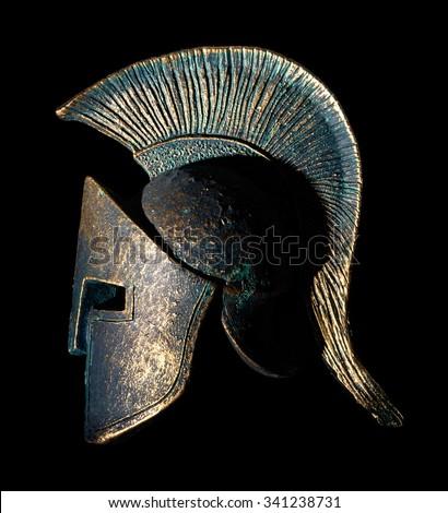Ancient greek Sparta style helmet souvenir isolated on a black background, studio shot - stock photo