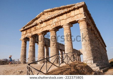 Ancient Greek temple with a tourist taking a picture in front of it. Segesta, Sicily. - stock photo