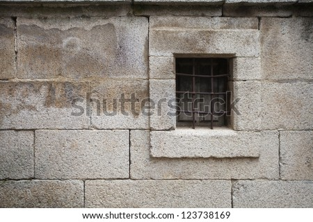 Ancient grilled window in stone wall