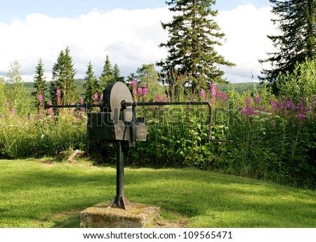 Ancient grindstone in a rural landscape - stock photo