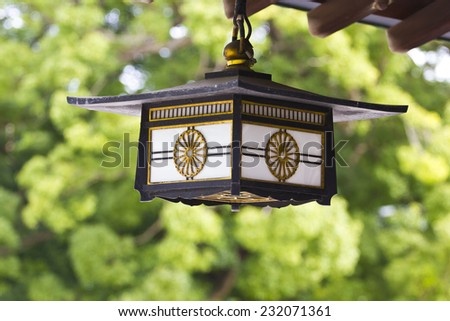 Ancient handmade ceiling lamp on a temple in Japan with a green forest background. - stock photo