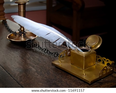 ancient inkwell and feather - stock photo