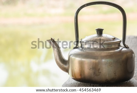 Ancient kettle placed on the old wooden floor. In the hut of a farmer. To boil water for tea and coffee. - stock photo
