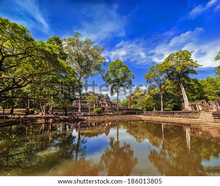 Ancient Khmer architecture. Outdoor park landscape with lake and panorama view of Baphuon temple ruins at Angkor Wat complex, Siem Reap, Cambodia - stock photo