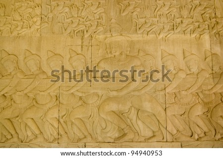 Ancient Khmer bas relief carving showing Hindu gods, or devas pulling on the snake Vasuki in the Churning of the Ocean of Milk legend.  Angkor Wat Temple, Siem Reap, Cambodia. - stock photo