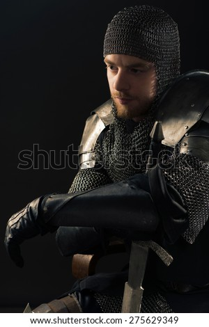 Ancient knight in metal armor with sword - stock photo