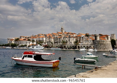 Ancient Korkula town and a few boats anchored in the harbor - stock photo