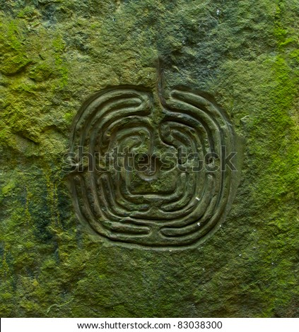Ancient labyrinth cut in stony wall to help you find a way from maze - stock photo