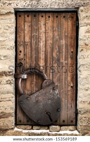 Ancient locked wooden door and big rusted padlock, old fashioned safety concept