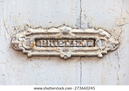 Ancient mailbox with the Dutch text for letters engraved on a white door - stock photo