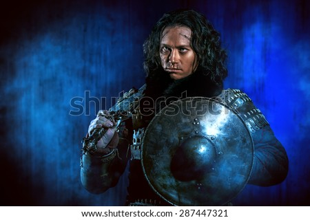 Ancient male warrior in armor holding sword and shield. Historical character. Fantasy.