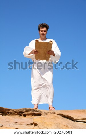 Ancient man in white robe reading from parchment scroll - stock photo
