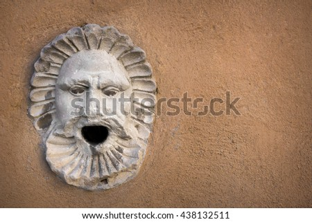Ancient marble sculpture depicting a head with an open mouth. - stock photo