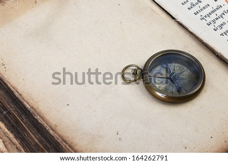 ancient mariner's compass and watch on old book