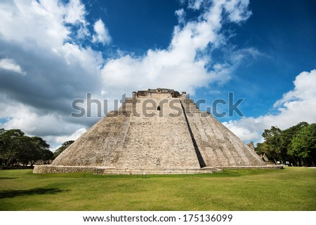 Ancient mayan pyramid of Ushmal in Mexico on the grass field with cloudy sky - stock photo