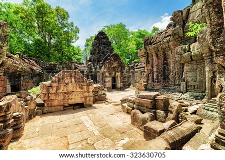 Ancient mossy buildings with carving of Ta Som temple on blue sky background. Enigmatic Ta Som nestled among rainforest in Angkor, Siem Reap, Cambodia. Amazing Angkor is a popular tourist attraction. - stock photo