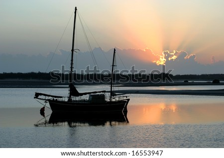 Ancient old ketch moored peacefully at sunrise. - stock photo