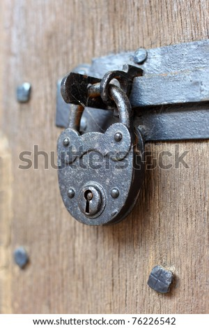 Ancient padlock at a wooden door - stock photo
