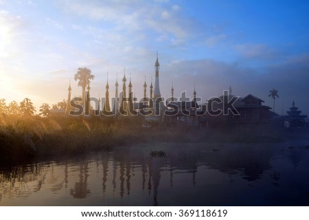 Ancient pagoda and monastery over mist on Inle lake, Shan state, Myanmar - stock photo