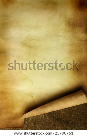 Ancient paper with curl on wooden table close up - stock photo