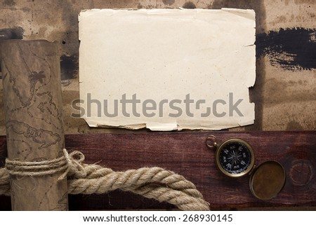 Ancient parchment with a map, compass, and ship ropes. - stock photo