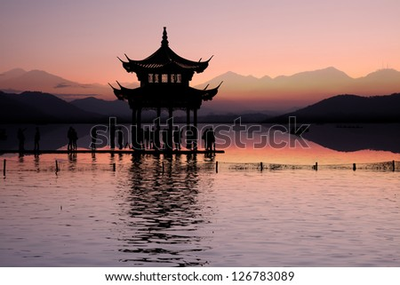 ancient pavilion on the west lake with sunset in hangzhou,China. - stock photo