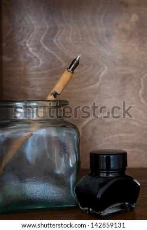 ancient pen and vintage ink pot on wooden background - stock photo