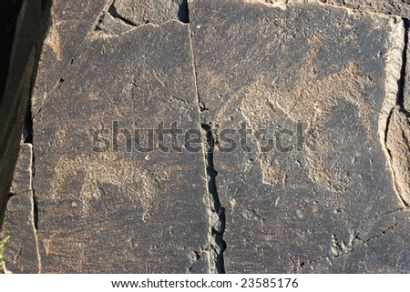 Ancient petroglyphic image of two hunters on horses. Area Tamgaly. - stock photo