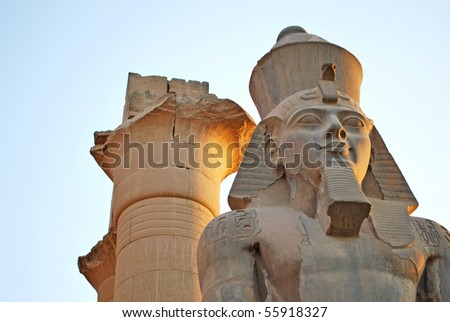 ancient Pharaoh statue and column on backlighted sky background - stock photo