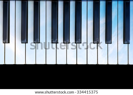 Ancient piano keys colored as sky on black background - stock photo