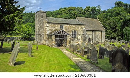 Ancient picturesque rural Saxon church, St. Gregory's Minster, in Kirkdale near Kirkbymoorside, North Yorkshire, England - stock photo