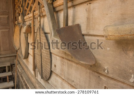 Ancient plough of Thai farmer and other vintage local utensils hanging on old wooden wall