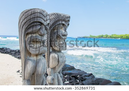 Ancient Polynesian style tiki wooden carvings along the beach greet visitors (tourists) to Ki'i Pu'uhonua O Honaunau National Park on the Big Island of Hawaii, an historic travel destination.