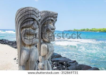 Ancient Polynesian style tiki wooden carvings along the beach greet visitors (tourists) to Ki'i Pu'uhonua O Honaunau National Park on the Big Island of Hawaii. - stock photo