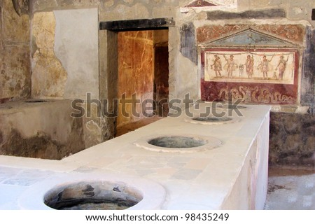 Ancient Pompeii - Thermopolium of Asellina with old food serving counter and fresco - stock photo