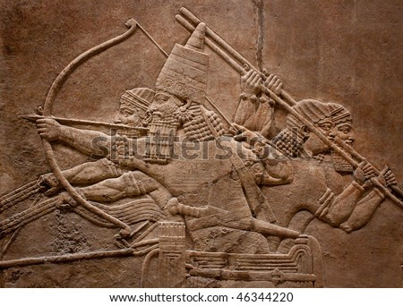 Ancient relief of assyrian warriors fighting in the war with bows,arrows and spears - stock photo
