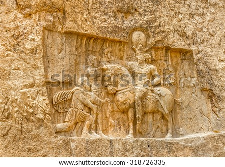 Ancient relief of the necropolis Naqsh-e Rustam that shows the triumph of Shapur I over the Roman Emperor Valerian and Philip the Arab, near ruins of Persepolis. - stock photo