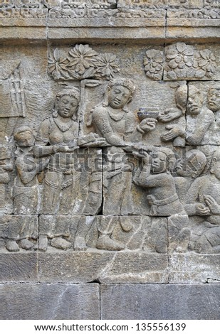 Ancient religious sculpture of a group of woman worshiper on the sandstone wall of the Borobudur temple in Jogjakarta, Indonesia.
