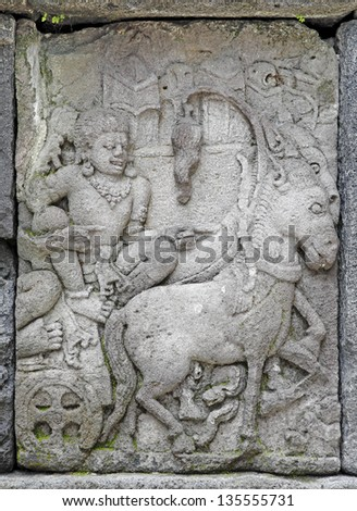Ancient religious sculpture of a man riding a horse chariot on the sandstone wall of the exotic Prambanan Temple in Jogjakarta, Indonesia. - stock photo