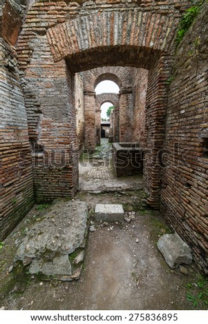 Ancient roman arches in row with alley and brick walls, weathered but restored, heritage of early italian history, now travel destination for tourists. Ostia old town, Rome, Italy. - stock photo