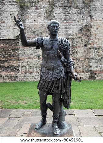 Ancient Roman monument statue of the Emperor Trajan in front of wall, London England UK United Kingdom archeology Rome - stock photo