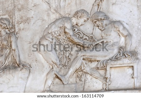 Ancient roman sculpture of the hero Achilles healing Telephus (the son of Hercules) with the spear that caused the wound - stock photo