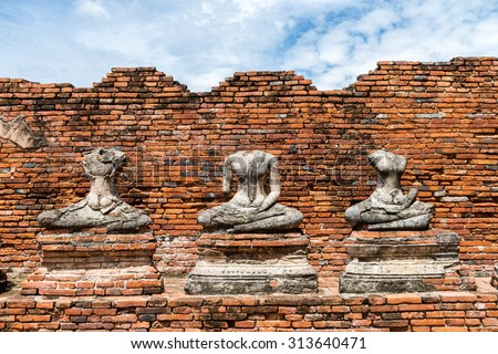 ancient ruin buddha sculpture with brick wall background in Ayutthaya, Thailand - stock photo