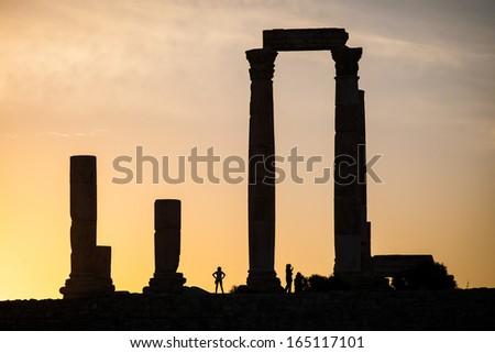 Ancient ruins in the citadel of Amman, Jordan silhouette of women at the Temple of Hercules - stock photo