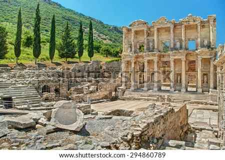 ancient ruins of Celsus library in Ephesus near green hill with cypress trees on sunny day, Turkey - stock photo