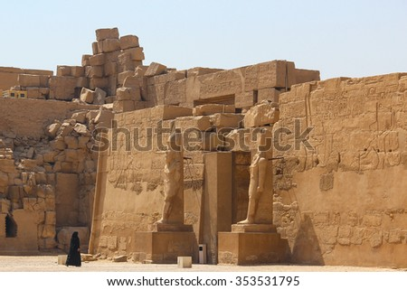Ancient ruins of Karnak temple the woman in black goes to the temple. - stock photo