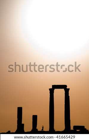 ancient ruins with sun and sunset sky in background (Temple of Hercules in Amman, Jordan)