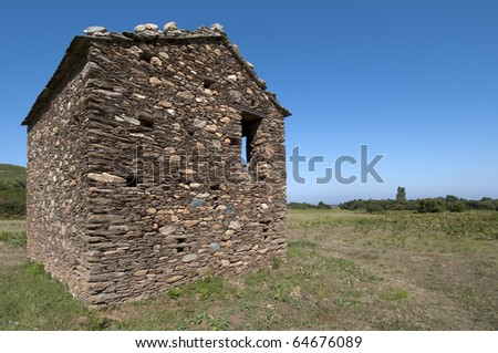 Ancient rural house in ruins on a green field