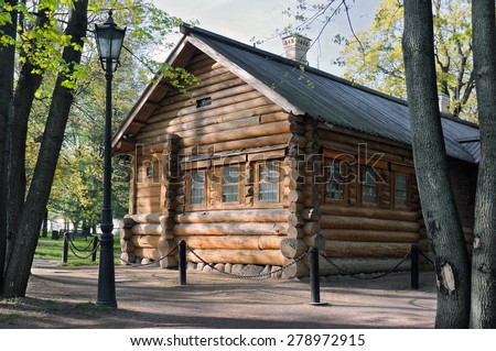 Ancient Russian wooden house from logs among old trees. - stock photo