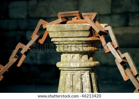ancient rusty chain and stone column in santiago de compostela, galicia, spain - stock photo